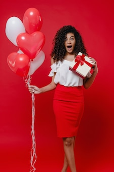 Excited black woman with heart shaped colorful balloons and valentine gift on red wall