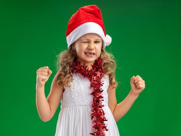Взволнованная моргнула маленькая девочка в новогодней шапке с гирляндой на шее, показывая жест да, изолированный на зеленом фоне