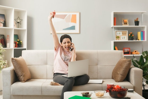 Excited blinked raising hand young girl with laptop speaks on phone sitting on sofa behind coffee table in living room