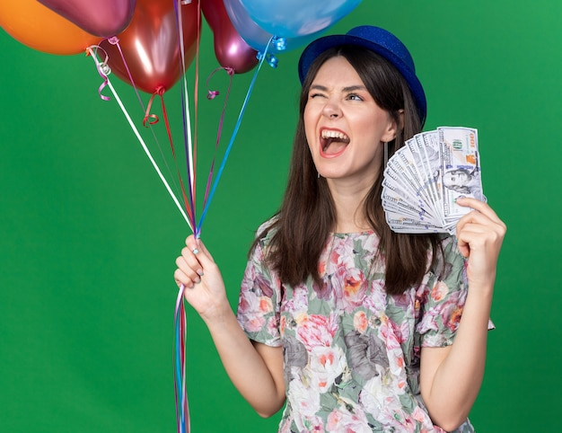 現金で風船を保持しているパーティーハットを身に着けている興奮したまばたき若い美しい少女