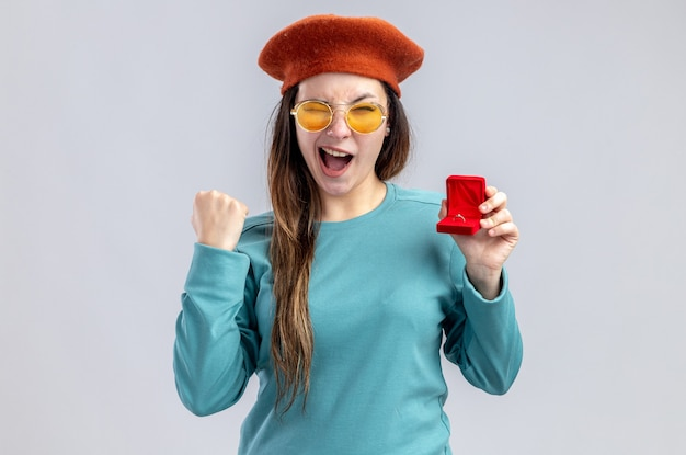 Excited blinked young girl on valentines day wearing hat with glasses holding wedding ring showing yes gesture isolated on white background