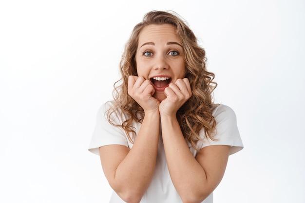 Eccitato donna bionda urla di gioia e sorpresa, vincendo e festeggiando, gridando di felicità e stupore, in piedi in maglietta sul muro bianco