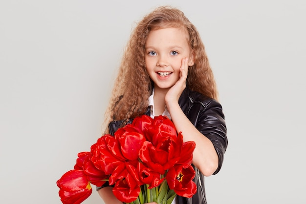 Excited blonde female child in black leather jacket holding bouquet of red tulips, telling something and keeping hand near mouth