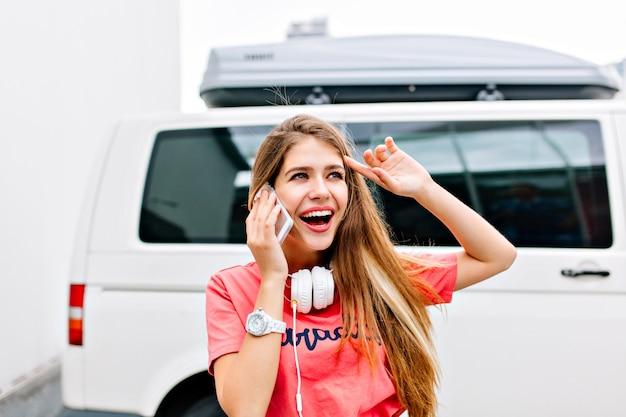 ピンクのシャツと白いヘッドフォンを身に着けている興奮したブロンドの女の子が友人と電話で話し、遠くを見ている