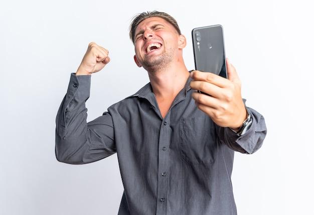 Eccitato bell'uomo biondo che tiene il telefono e tiene il pugno alzato