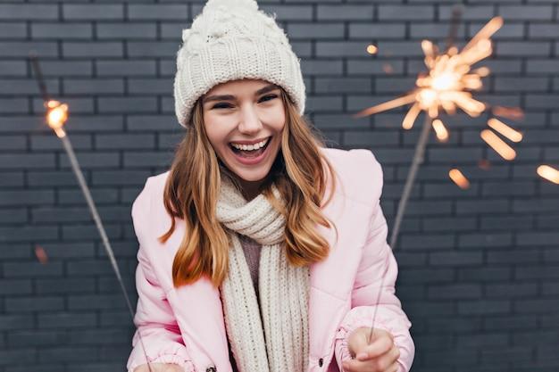 새 해를 축 하하는 낭만적 인 복장에 흥분된 금발 여자. 크리스마스에 놀 아 요 니트 모자에 명랑 소녀의 야외 사진.
