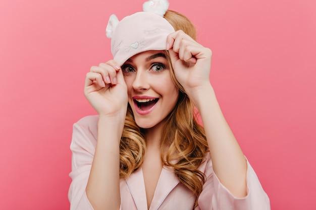 青い目と笑いで興奮した金髪の女性。幸せを表現するアイマスクで素敵な女性の屋内クローズアップの肖像画。