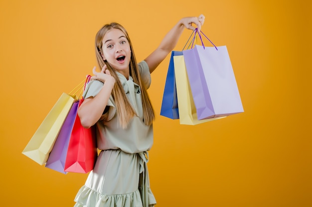 Excited blonde woman with colorful shopping bags isolated over yellow