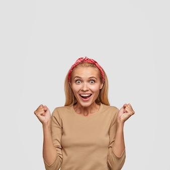 白い壁にポーズをとって興奮した金髪の若い女性