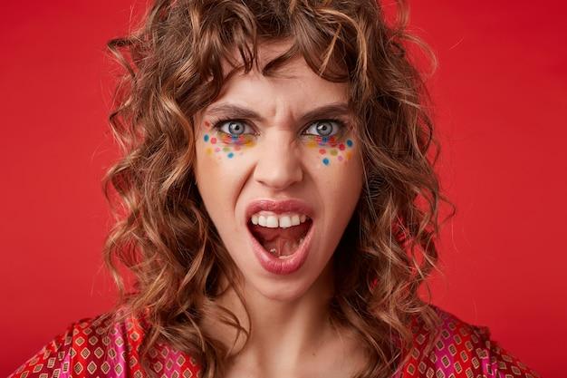 Eccitata giovane femmina riccia dagli occhi blu con punti multicolori sul viso guardando con la bocca larga aperta e aggrottando le sopracciglia, isolate