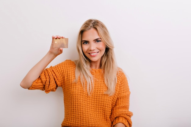 Excited blue-eyed woman in knitted jumper holding golden bank card and laughing