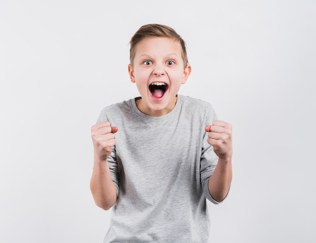 Excited boy clenching his fist standing against white backdrop