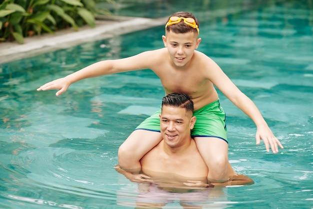 Взволнованный мальчик в очках прыгает в воду с плеч своего отца, стоящего в бассейне