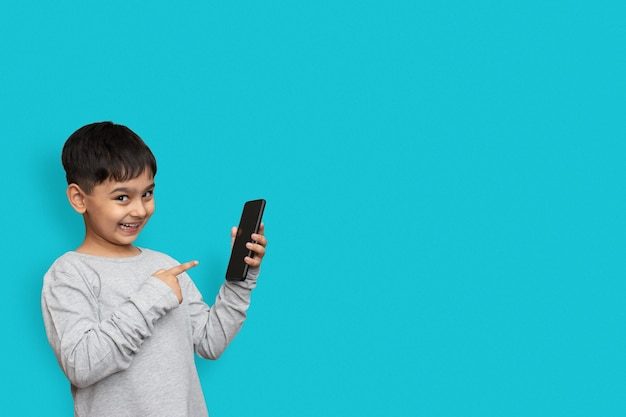 Excited boy smiling and poiting at screen on smartphone. on plain blue background with copy space