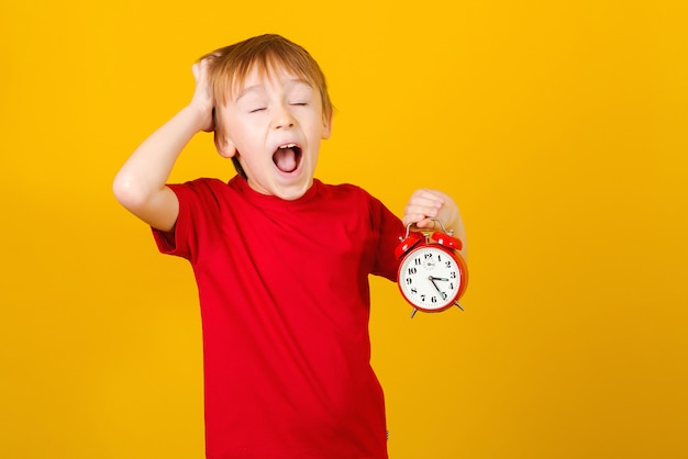 Excited boy with clock. hurry up. shocked kid holding alarm clock, over yellow. screaming little boy.