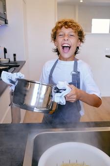 キッチンで鍋料理をしている興奮した少年