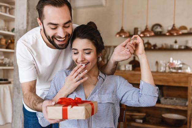 興奮したブルネットのカップルの男性と女性がプレゼントボックスとテーブルに座っている間アパートで朝食をとる