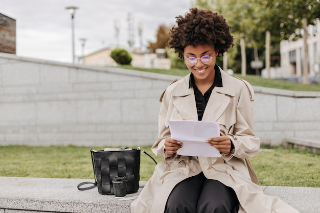 Excited brunette dark-skinned woman in eyeglasses and beige trench coat smiles, holds paper sheet and sits outdoors
