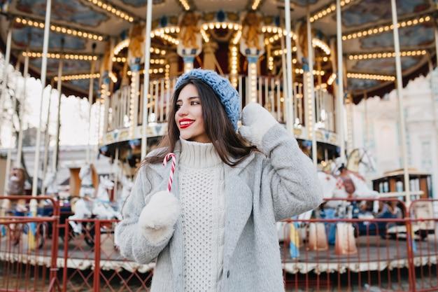Eccitato ragazza bruna in sfocatura cappello lavorato a maglia in attesa di un amico nel parco di divertimenti in giornata invernale. foto all'aperto di donna felice con i capelli scuri tenendo il bastoncino di zucchero e in posa davanti alla giostra.