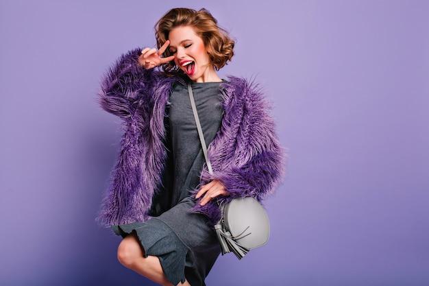 Eccitata ragazza bruna in abito grigio ballando con il sorriso su sfondo viola