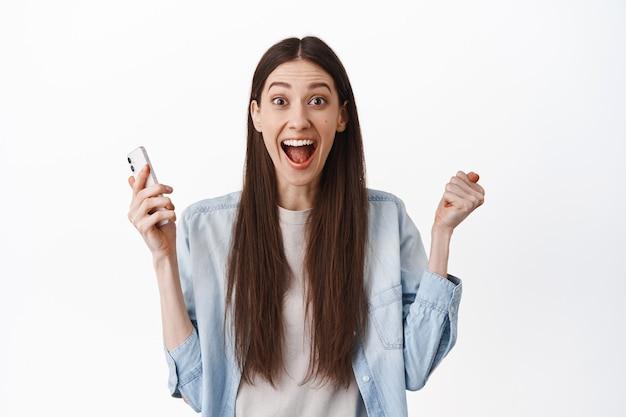 Eccitata ragazza bruna urla stupita, tiene in mano lo smartphone e festeggia, vince online, riceve grandi notizie, raggiunge l'obiettivo dell'app, in piedi sul muro bianco