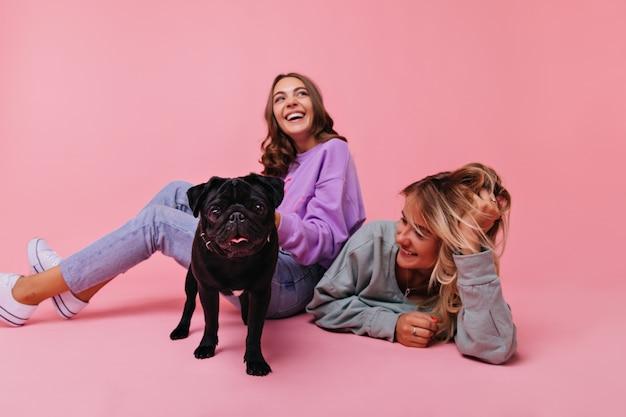 검은 불독과 함께 바닥에 앉아 흥분된 갈색 머리 소녀. 귀여운 애완 동물과 함께 재미 두 여자 친구의 실내 초상화.