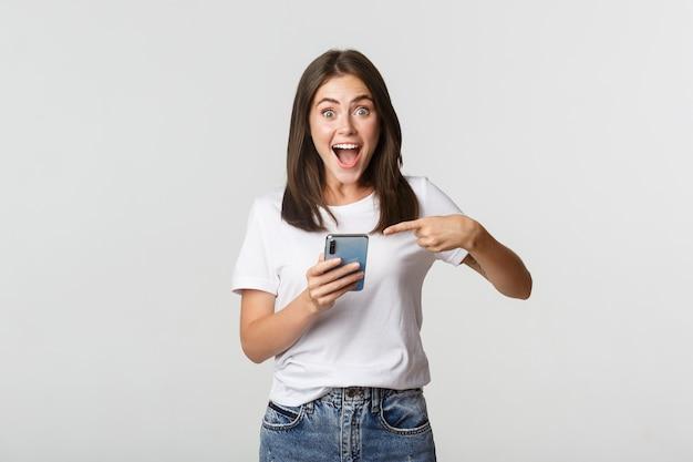 興奮したブルネットの少女は驚いて笑顔でスマートフォンの画面を指しています。