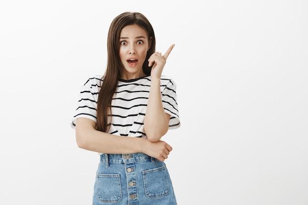 Emozionante piano di pensiero ragazza bruna, avere un'idea o suggerimento, alzando il dito indice
