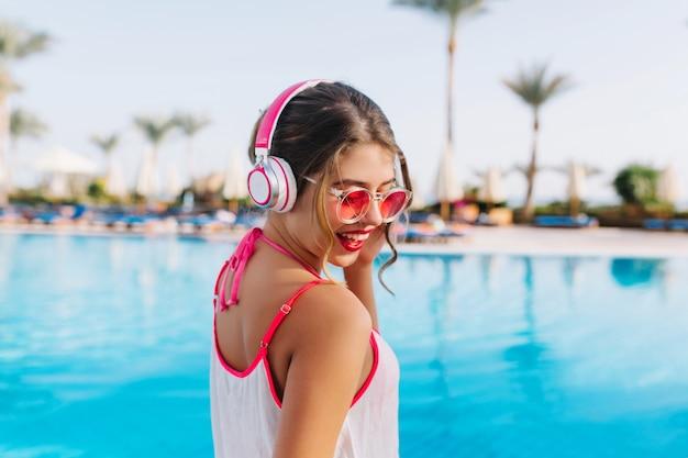 Eccitata ragazza bruna con la pelle abbronzata che ascolta favorendo la musica mentre prende il sole in piscina all'aperto