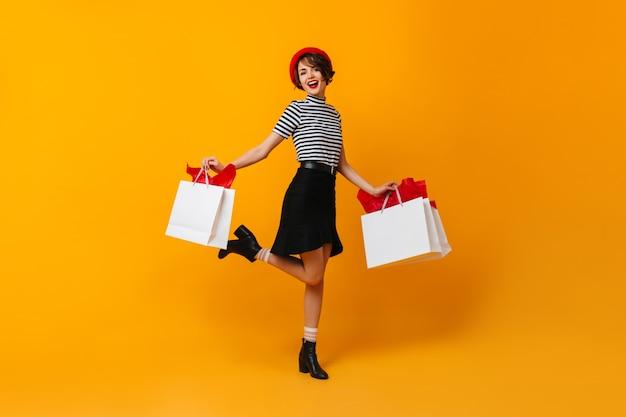 Signora castana emozionante che balla con le borse del negozio