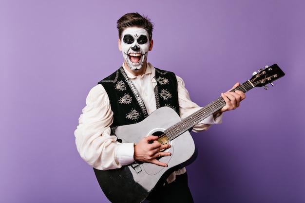 Возбужденный брюнет с макияжем зомби поет на фиолетовой стене. снимок парня muerte, играющего на гитаре и смеющегося в помещении.