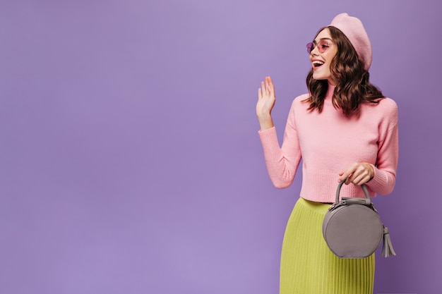 Eccitato donna bruna in gonna verde, berretto rosa e maglione onde mano in segno di saluto