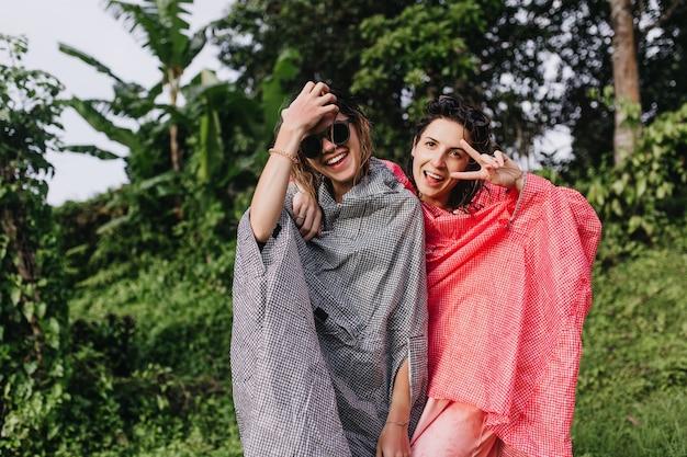 가장 친한 친구와 재미 핑크 비옷에 흥분된 갈색 머리 여자. 이국적인 숲에서 시간을 보내는 사랑스러운 자매의 야외 사진.