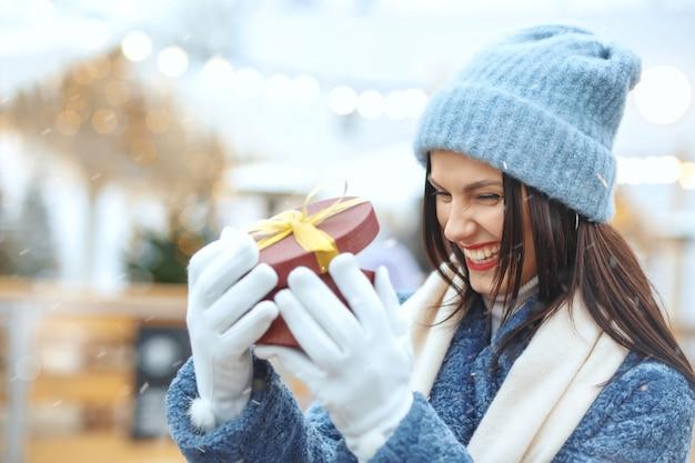 降雪時のクリスマスフェアでギフトボックスを保持している冬のコートで興奮したブルネットの女性。テキスト用のスペース