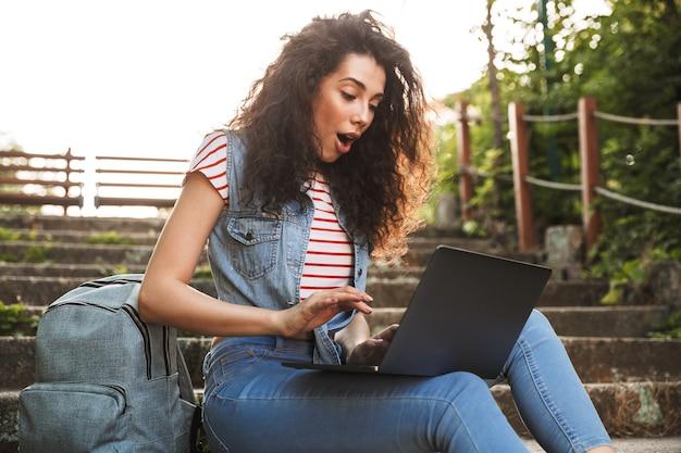 夏の日に公園の階段に座って、驚きと銀のラップトップを使用して興奮したブルネットの女性