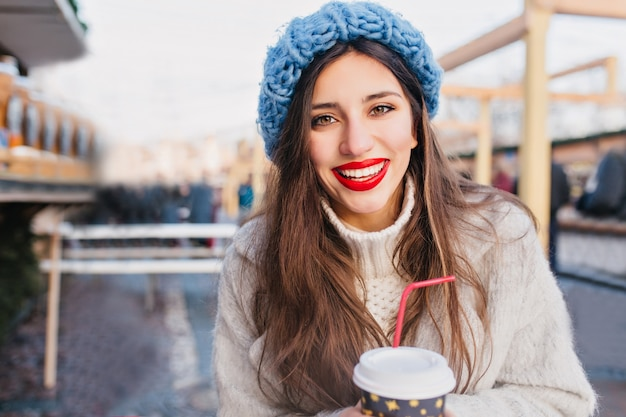 Excited brunette woman with brown eyes drinking tea on blur city. outdoor photo of gorgeous dark-haired lady in coat and blue hat holding cup of hot coffee in cold day.