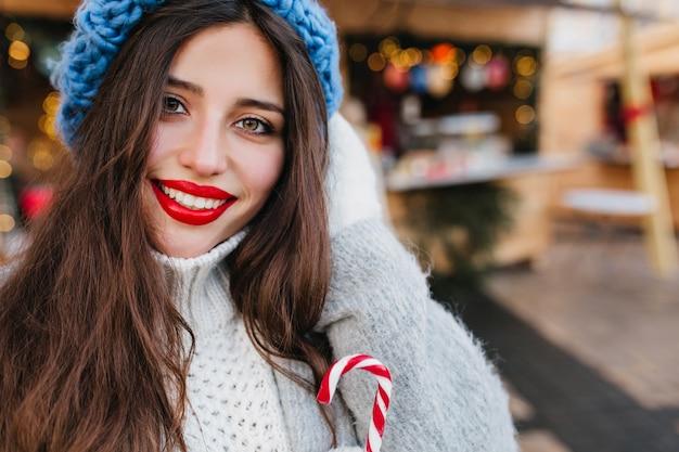 通りをぼかしにお茶を飲んで茶色の目で興奮してブルネットの女性。寒い日にホットコーヒーのカップを保持しているコートと青い帽子でゴージャスな黒髪の女性の屋外写真。