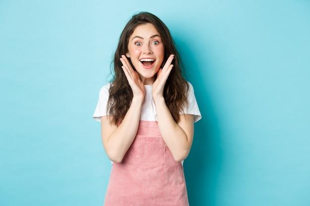 かわいい巻き毛の髪型で興奮したブルネットの女性は、あえぎ驚いて驚いて、カメラに驚いて見え、サプライズギフトを獲得または受け取って、青い背景の上に立っています。