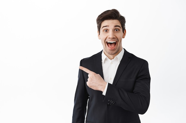 Excited business man, corporate entrepreneur in suit gasping amazed, pointing aside at copyspace with impressed smiling face, checking out awesome deal, white wall