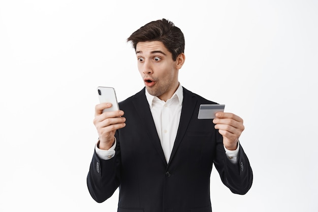 Excited business man in suit look at his phone, reading screen with amazed face and holding credit card, log in to online banking app, standing over white wall