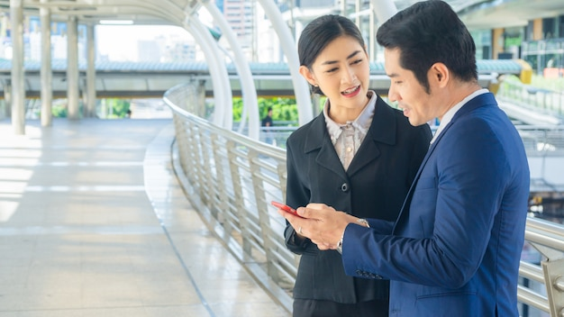 Excited business man and woman receiving good news on line in a smart phone outside on outdoor