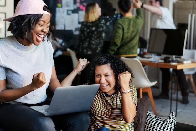 노트북 화면을 보고 있는 흥분된 비즈니스 사람들