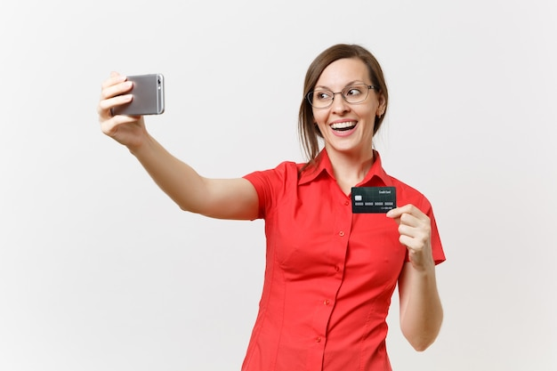 クレジット銀行カード、白い背景で隔離のキャッシュレスのお金で携帯電話で自分撮りショットを撮っている赤いシャツを着た興奮したビジネス女性。高校大学の概念における教育教育。