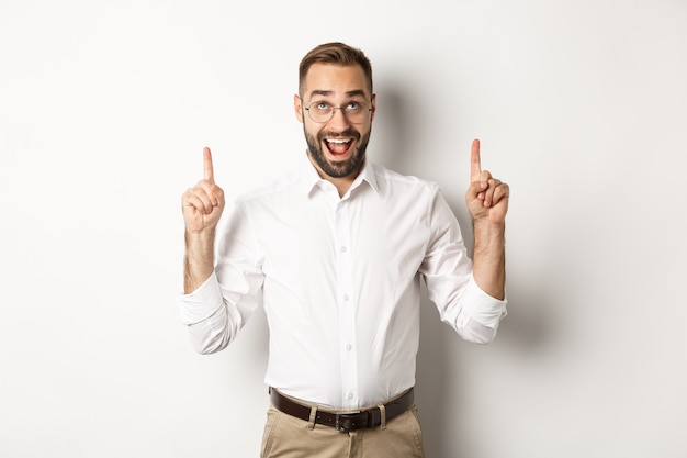 Excited businessman checking out advertisement, pointing and looking up with happy face, standing against white background.