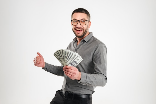 Excited businessman holding money.