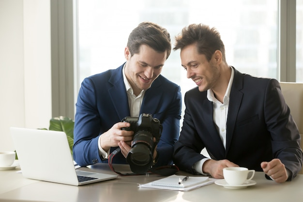 Excited businessman holding professional camera, showing photogr