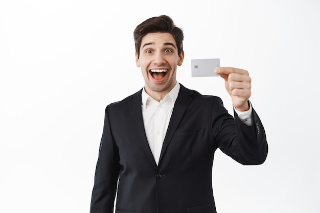 Excited businessman shows credit card and smiling, opened deposit, standing against white wall in black suit