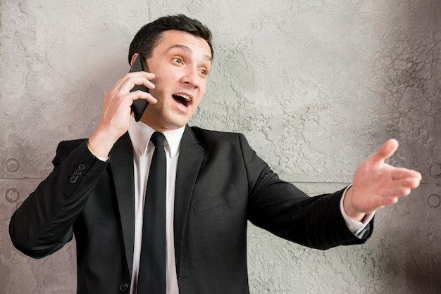 Excited businessman speaking on phone and pointing away