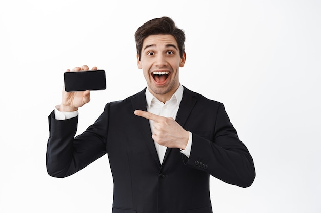Excited businessman in suit points at empty phone screen horizontal, showing smartphone app promo, standing over white wall