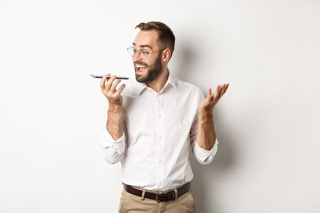 スピーカーフォンで話し、笑顔で、白い背景の上に立って、恍惚とした顔で音声メッセージを録音する興奮したビジネスマン。